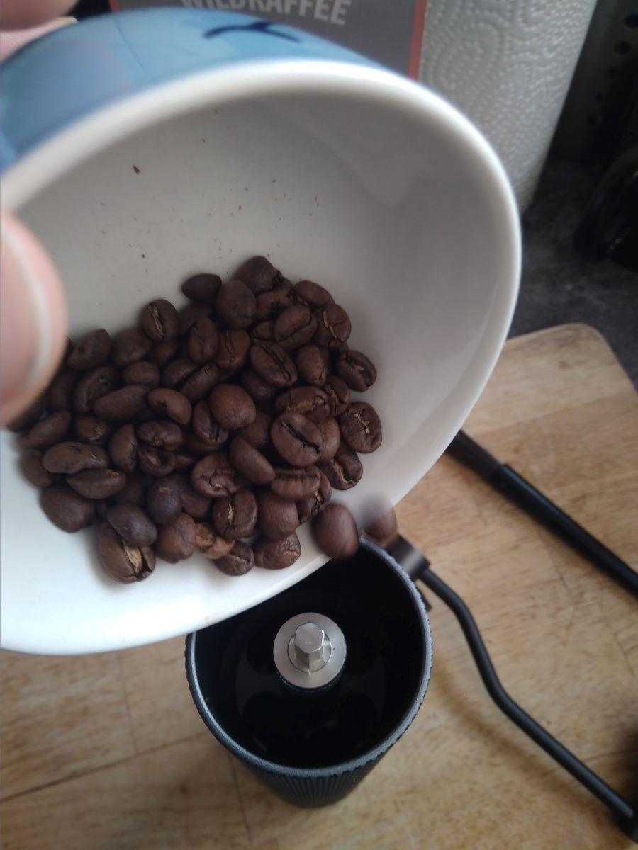 Frische Bohnen in der Handmühle mahlen
